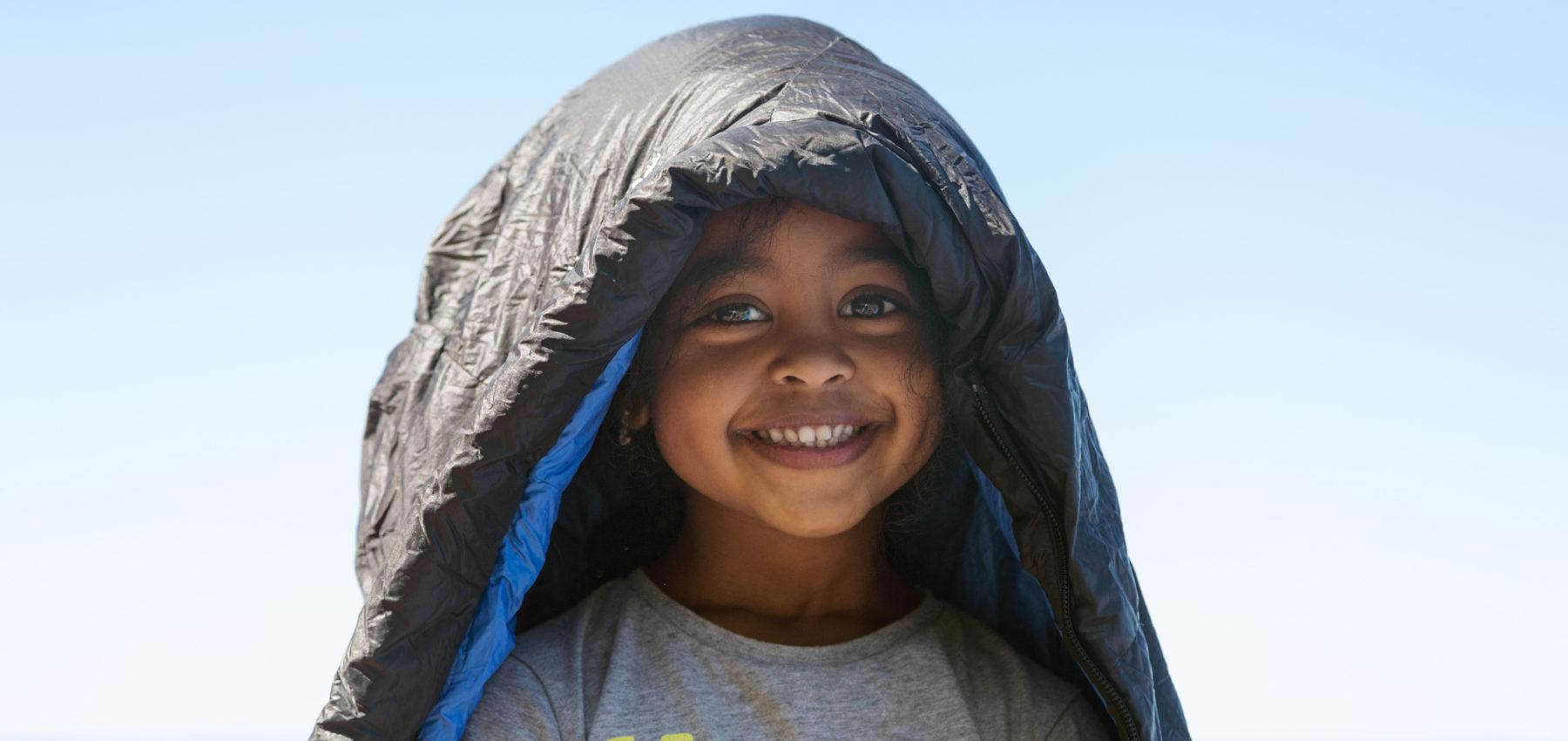 Barn smiler og ser inn i kameraet, på hodet har hun en sovepose.