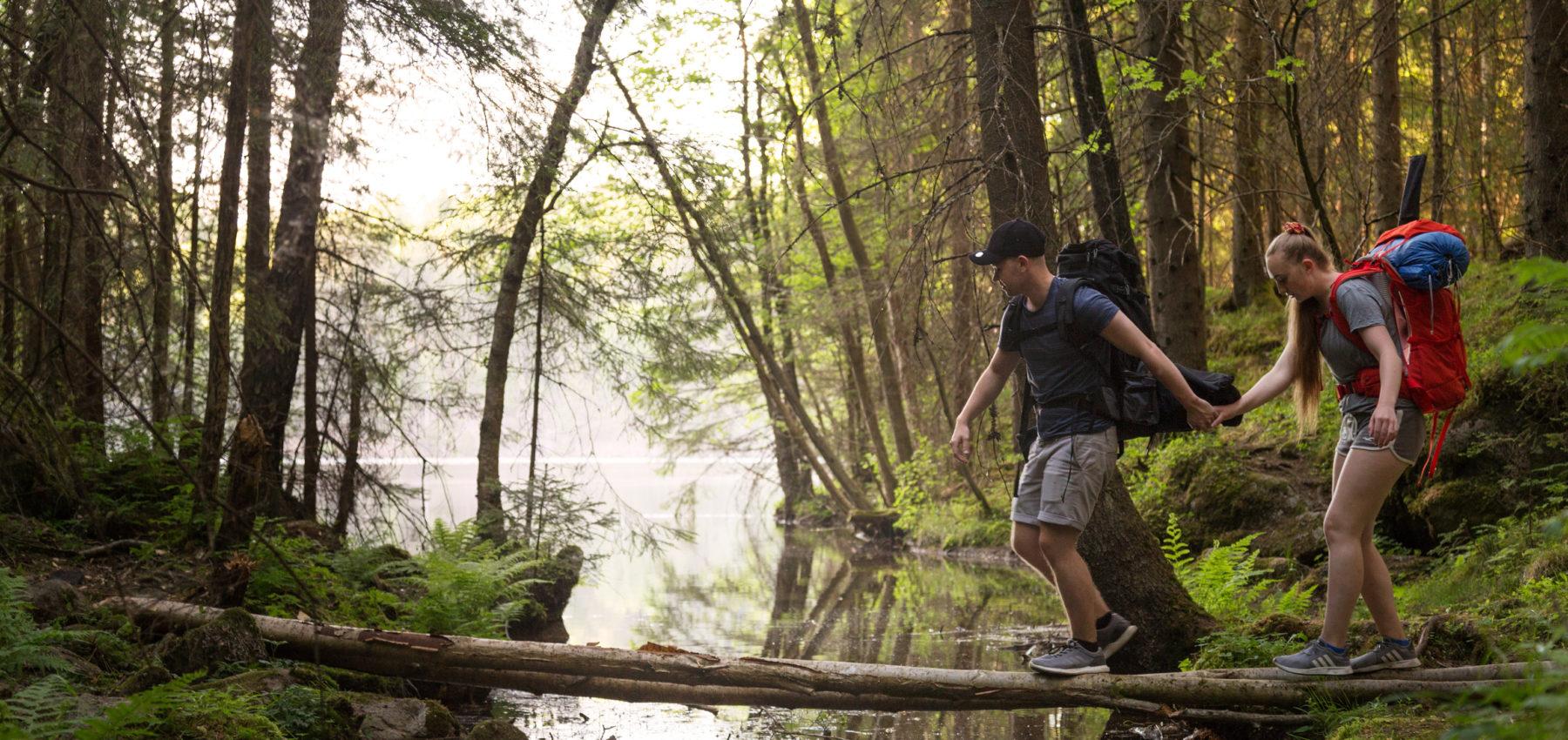 En gutt og en jente holder hender og går over en smal plankebro over en elv.