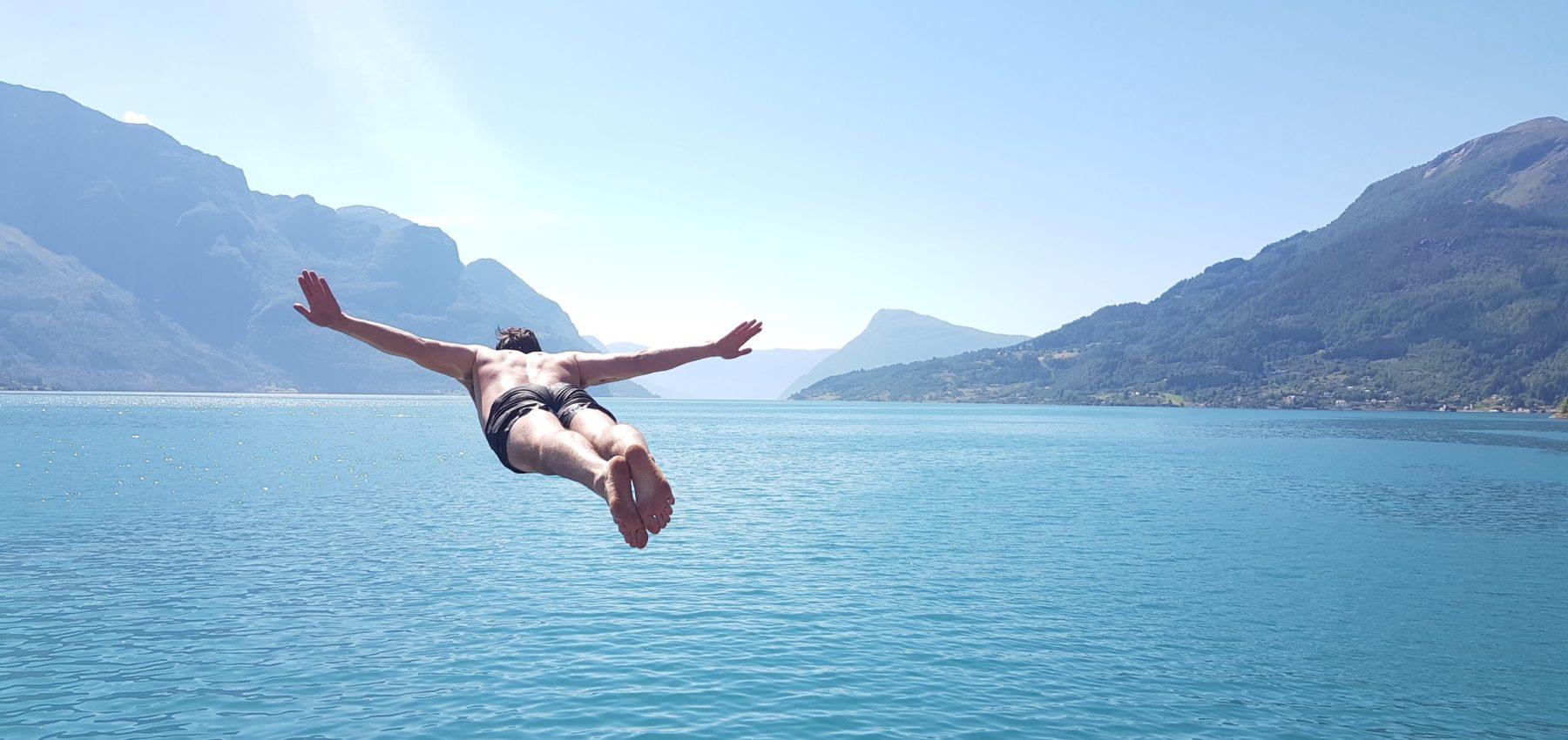 Mann stuper i fjor med blått klart vann. På bildet er han midt i stupet med hendene spredd utover, som om han flyr.