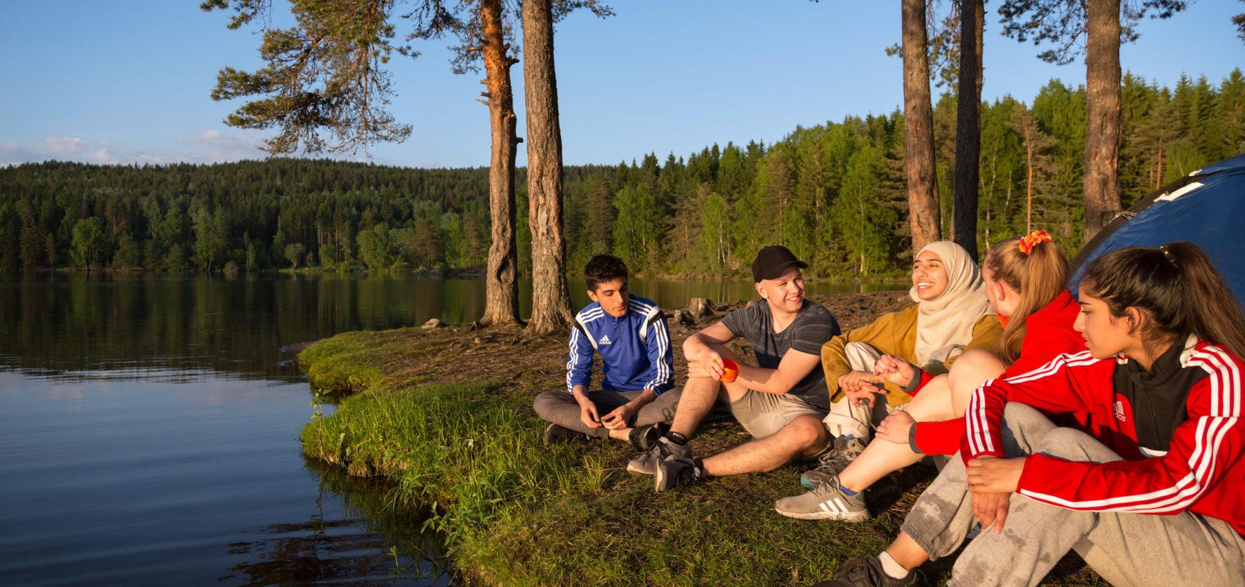 Ungdommer sitter foran telt ved et skogvann.