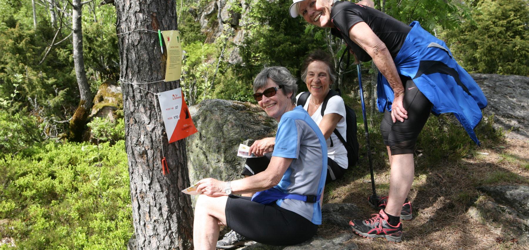 Tre damer på turorientering i skogen, smiler og ser inn i kamera.