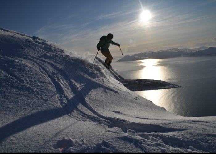 Mann på ski med sola i bakgrunnen