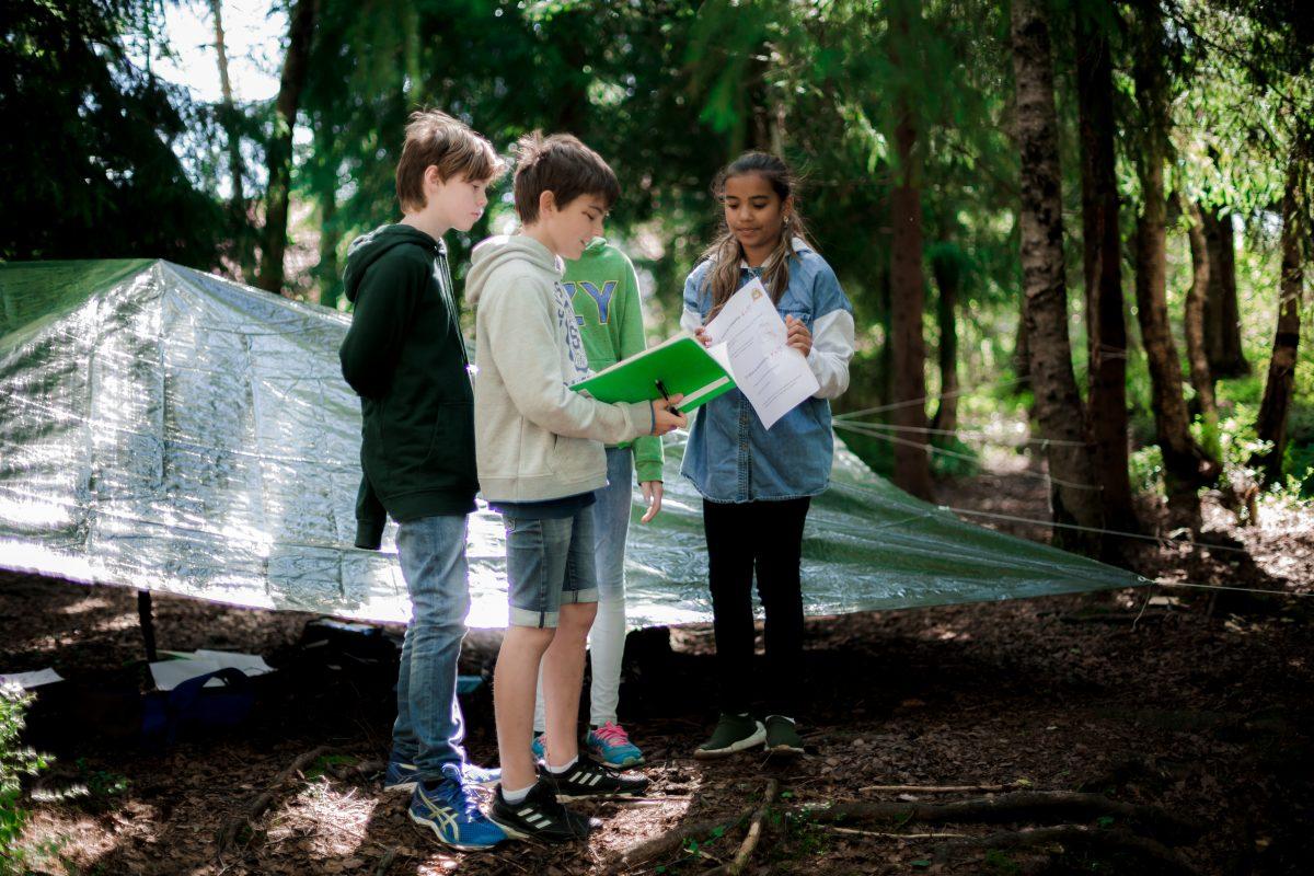 Barn ute i naturen med skolebøker i hendene