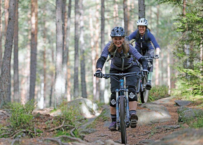 To jenter sykler på sti.
