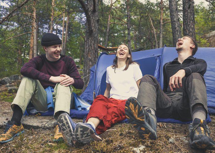 Tre ungdommer foran et telt